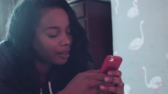 afro american female in bed with smart phone - afro caribbean ethnicity stock videos and b-roll footage