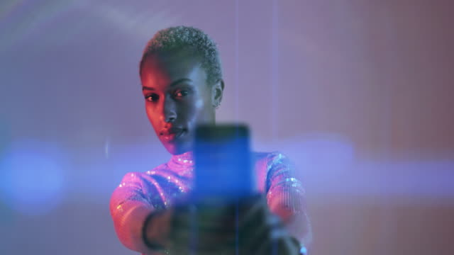 afro american female in colorful bright lights taking picture with smart phone - neon stock videos & royalty-free footage