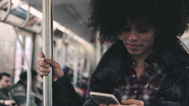 afro american female on subway with smart phone - öffentliches verkehrsmittel stock-videos und b-roll-filmmaterial