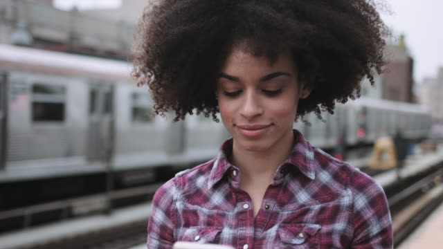 afro american female standing on train platform with mobile phone - stazione della metropolitana video stock e b–roll