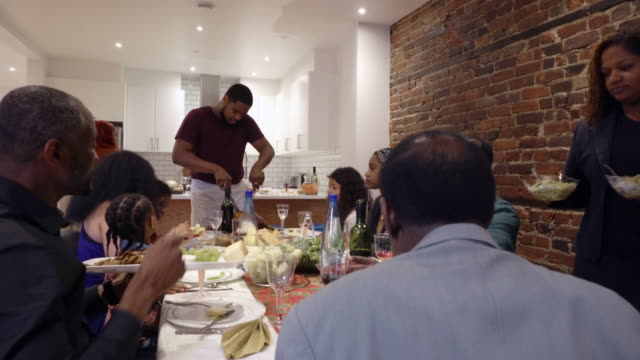 afro american large family sharing turkey diner for thanksgiving multi generations - dining table stock videos & royalty-free footage