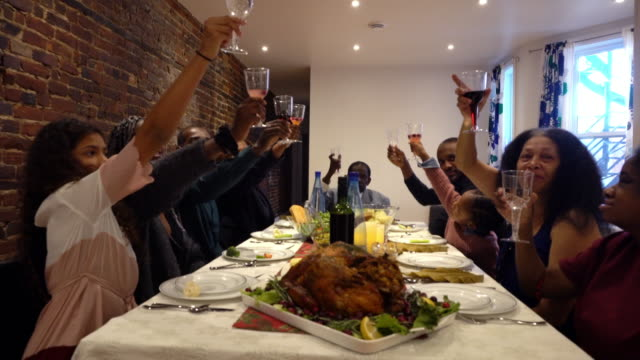 afro american large family toast diner for thanksgiving multi generations - mixed race person stock videos & royalty-free footage