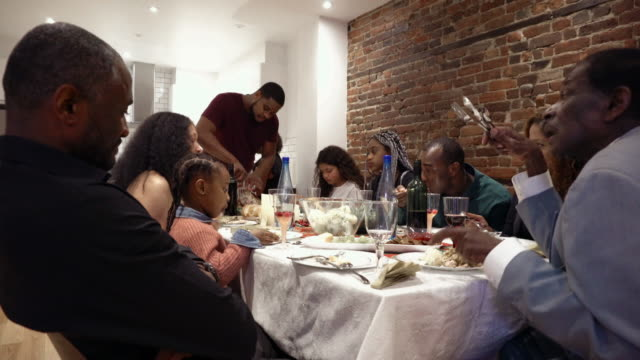afro american large family turkey diner for thanksgiving multi generations - dining table stock videos & royalty-free footage