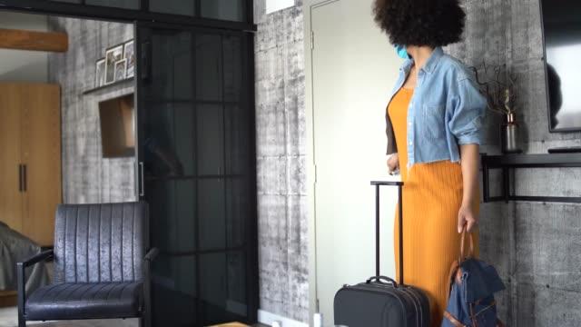 vídeos de stock e filmes b-roll de afro american tourist wearing a face mask to avoid the spread of coronavirus arriving at hotel room - sala de casa
