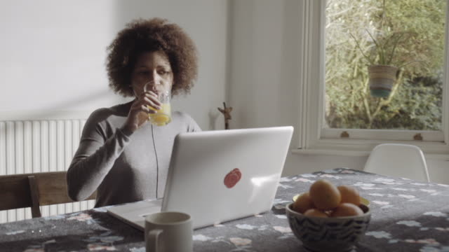 Afro American woman buying online on laptop in kitchen