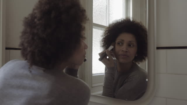 Afro American Woman in bathroom doing make-up in mirror