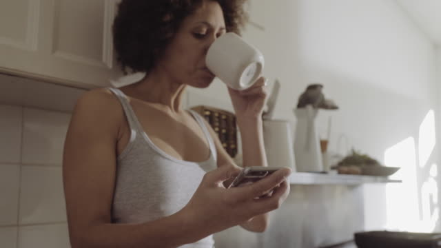 afro american woman in kitchen enjoying coffee in the morning - 小背心 個影片檔及 b 捲影像