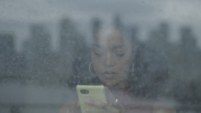 afro american woman influencer using smart phone and looking out of window on rainy day, with reflection of city skyline on window - mental illness stock videos & royalty-free footage