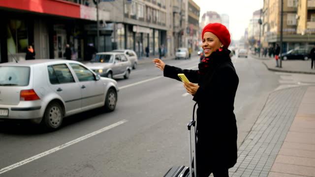 stockvideo's en b-roll-footage met afro amerikaanse vrouw die op een taxi door de straat wacht - bestellen
