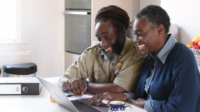 afro- caribbean couple using laptop at home to do home finances - 50 59 years stock videos & royalty-free footage