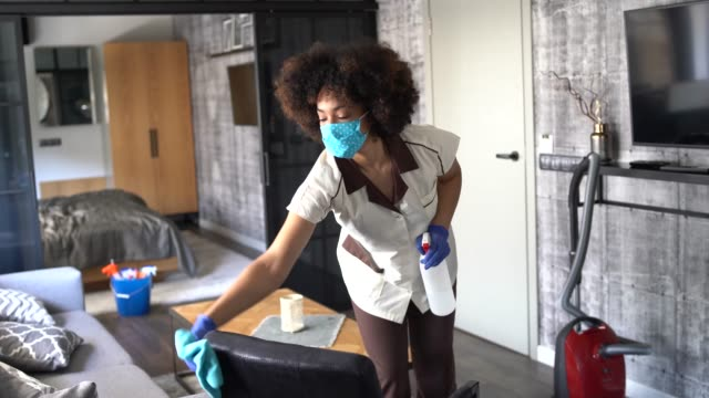 afro chambermaid wearing protective face mask and gloves while working at a hotel - hotel stock videos & royalty-free footage