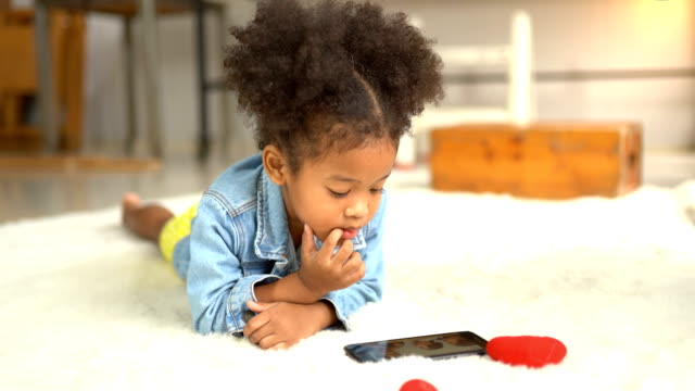 afro child playing on smartphone - internet of things stock videos & royalty-free footage