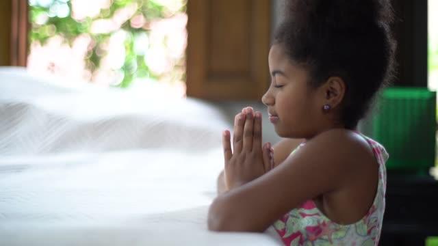 vídeos de stock, filmes e b-roll de afro criança rezando em casa - espiritualidade