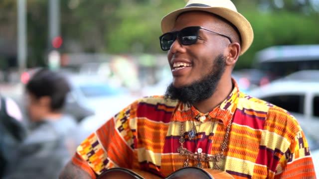 vídeos de stock, filmes e b-roll de homem de ascendência afro hippie com guitarra ao ar livre - violão acústico