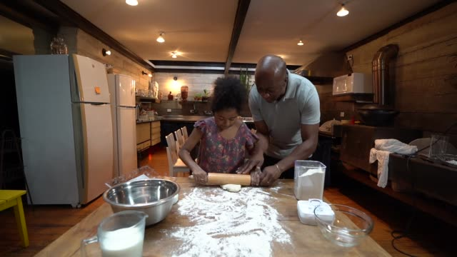 afro father teaching his daughter how to cook at home - pastry dough stock videos & royalty-free footage
