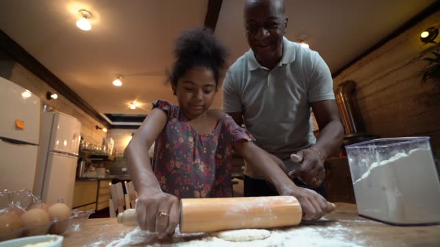 afro father teaching his daughter how to cook at home - afro hairstyle stock videos & royalty-free footage