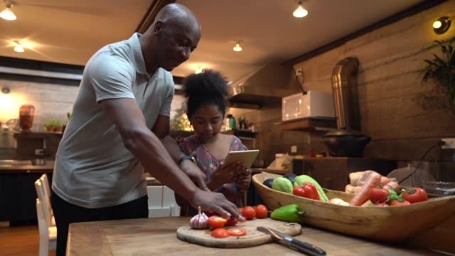 vídeos de stock, filmes e b-roll de afro pai ensinando sua filha a cozinhar em casa - cozinha
