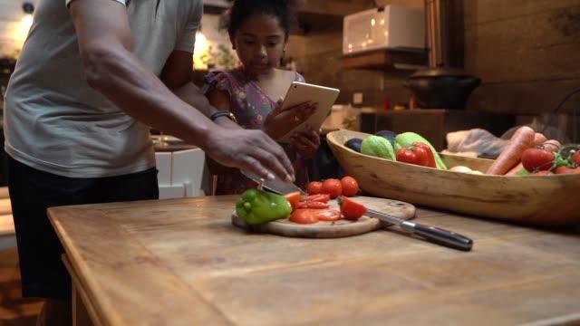 vídeos de stock, filmes e b-roll de afro pai ensinando sua filha a cozinhar em casa - avô