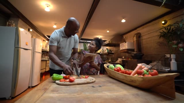 afro father teaching his daughter how to cook at home - encouragement stock videos & royalty-free footage