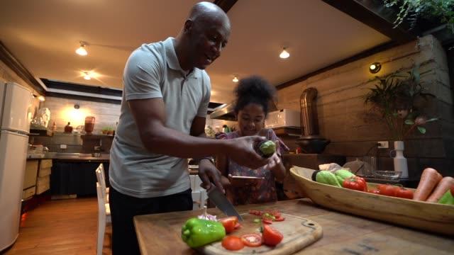 vídeos de stock, filmes e b-roll de afro pai ensinando sua filha a cozinhar em casa - preparando comida
