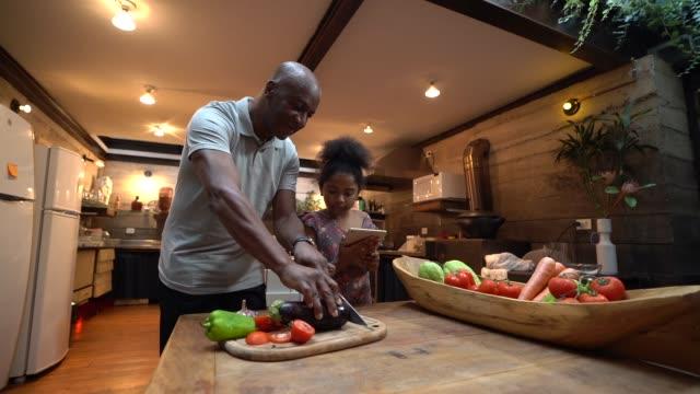 vídeos de stock, filmes e b-roll de afro pai ensinando sua filha a cozinhar em casa - receita