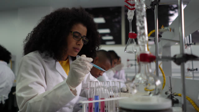 afro female student using a dropper to mix chemicals in test tubes during chemistry class - chemistry stock videos & royalty-free footage