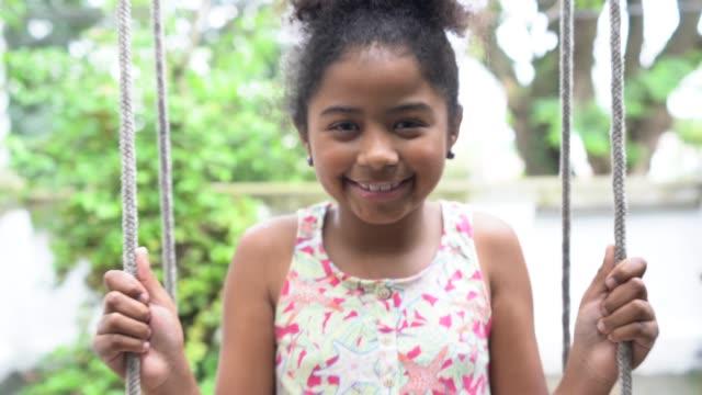 vídeos de stock e filmes b-roll de afro girl on swing at home portrait - equipamento de parque infantil