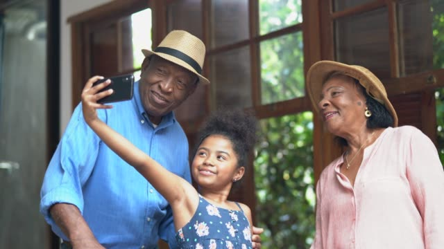 afro grandparents and granddaughter taking selfies in a hotel room - brazilian ethnicity video stock e b–roll