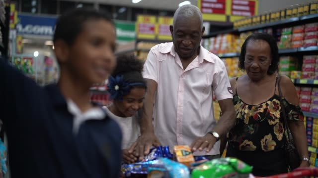 afro-hispanischen latino-familie im supermarkt kaufen - ungesunde ernährung stock-videos und b-roll-filmmaterial