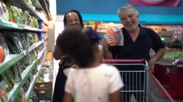 vídeos de stock, filmes e b-roll de afro latino latino neta e avós que compra no supermercado - comprar