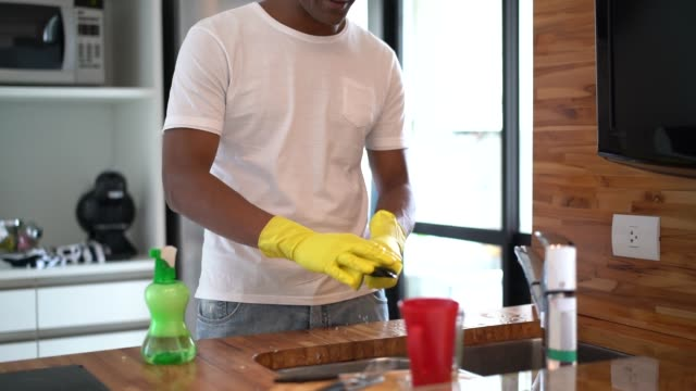 afro hispanic latino man washing the dishes at home - washing up glove stock videos & royalty-free footage