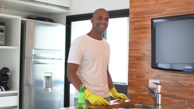 vídeos de stock, filmes e b-roll de afro latino latino homem lavando os pratos em casa - lavando