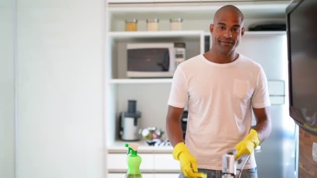 vídeos de stock e filmes b-roll de afro hispanic latino man washing the dishes at home - domestic kitchen