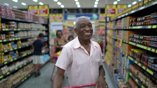 vídeos de stock e filmes b-roll de afro hispanic latino senior man portrait at supermarket - um dia na vida de