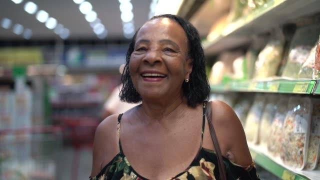 afro hispanic latino senior woman portrait at supermarket - afro stock videos & royalty-free footage
