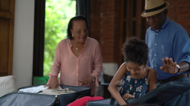 afro hispanic-latino grandparents and granddaughter packing for a trip - african american ethnicity stock videos & royalty-free footage