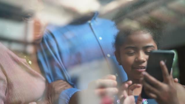 vídeos de stock, filmes e b-roll de afro latino-hispânica avós e neta usando telefone celular - afro