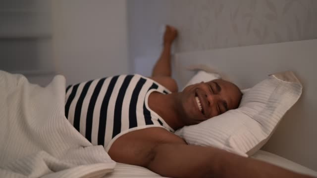afro latin man waking up - bedroom stock videos & royalty-free footage