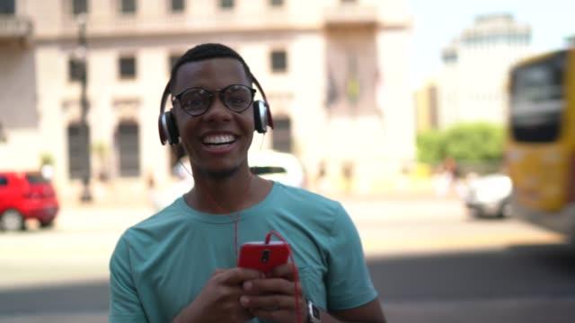 vídeos de stock, filmes e b-roll de afro latino usando móvel e ouvindo música na cidade - vida urbana