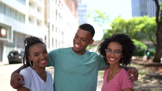vídeos de stock, filmes e b-roll de amigos novos latinos do afro que abraçam o retrato na cidade - três pessoas