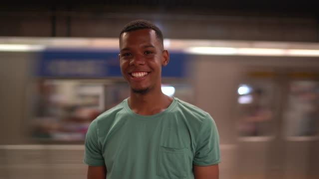 vidéos et rushes de portrait de jeune homme latine afro à la station de métro - véhicule utilitaire et commercial