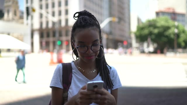 afro latin young woman in the city using smartphone portrait - dreadlocks stock videos & royalty-free footage