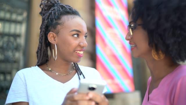 vídeos de stock, filmes e b-roll de afro latino jovens usando smartphone na cidade - estudante universitária
