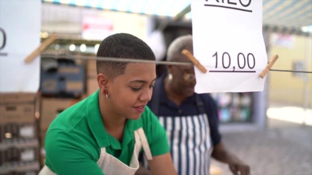 vídeos de stock e filmes b-roll de afro mother and daughter woman working in a street market - family business - vendedor trabalho no comércio