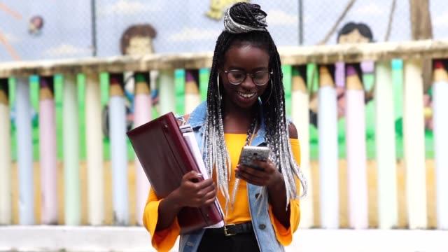 vídeos de stock, filmes e b-roll de aluno/professor afro em movimento com mobile - universidade