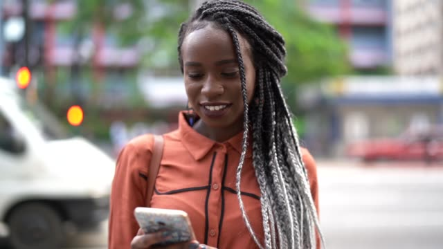 afro woman using mobile at street - black hair stock videos & royalty-free footage