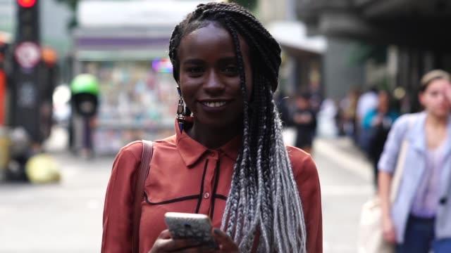 vídeos y material grabado en eventos de stock de mujer afro con móvil en la calle - pardo brasileño