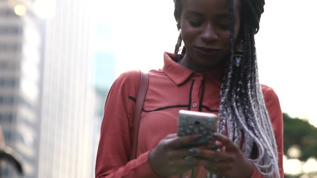 afro woman walking and using mobile at city - hipster person stock videos & royalty-free footage