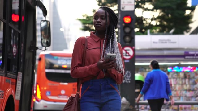 afro woman walking and using mobile at city - rastafarian stock videos and b-roll footage