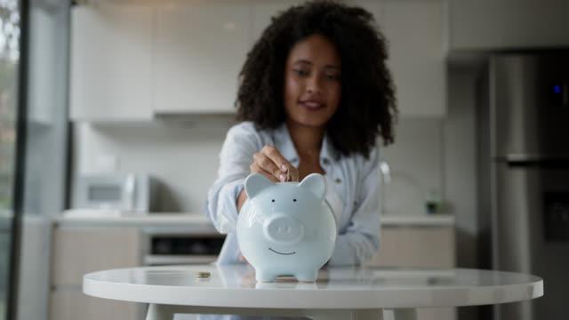 afro ung kvinna sätta in mynt i hennes spargris - savings bildbanksvideor och videomaterial från bakom kulisserna